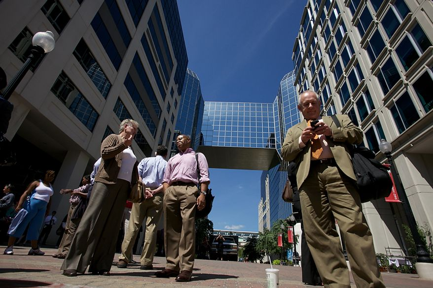 Office workers try to use their cellphones in Chinatown in Northwest after a 5.9 earthquake in Virginia is felt in Washington, D.C., Tuesday, August 23, 2011. (Andrew Harnik / The Washington Times)