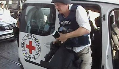 A journalist arrives at the Corinthia hotel after being evacuated from the Rixos Hotel in Tripoli in this image taken from television on Aug. 24, 2011. (Associated Press/APTN)