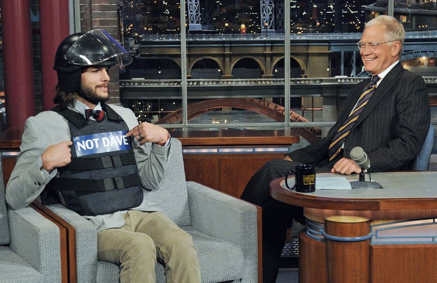 In light of a recent threat on a jihadist website against David Letterman, actor Ashton Kutcher wore a bulletproof vest and a helmet to a taping of the host's late-night talk show Wednesday. (CBS via Associated Press)