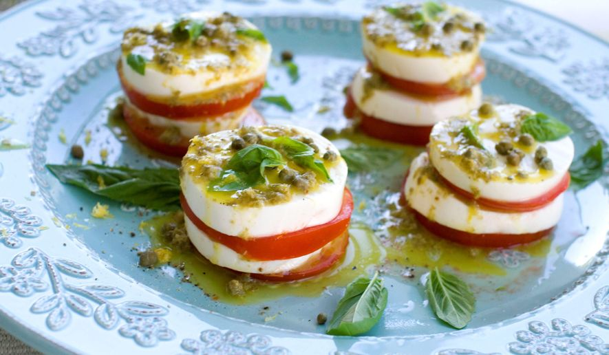 Tomatoes and fresh mozzarella are the star ingredients of caprese salad. To add a punch of tang, capers were added to the vinaigrette and a few more were sprinkled over the salad just before serving. (Associated Press)
