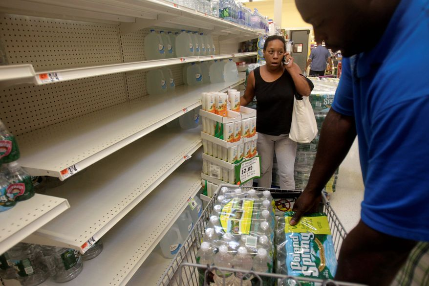 Shoppers stock up on water from rapidly emptying shelves in Far Rockaway, N.Y., Thursday. New York Mayor Michael R. Bloomberg urged residents living in low-lying areas to line up a place to stay on high ground ahead of a possible evacuation. (Associated Press)