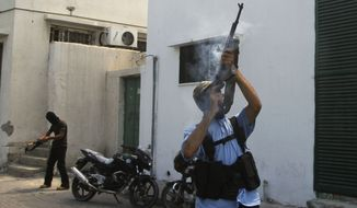 Masked Palestinian militants fire their rifles on Aug. 25, 2011, in Gaza City during the funeral of Islamic Jihad militant Ateya Mkat, 22, who was killed the day before in an Israeli air strike. (Associated Press)