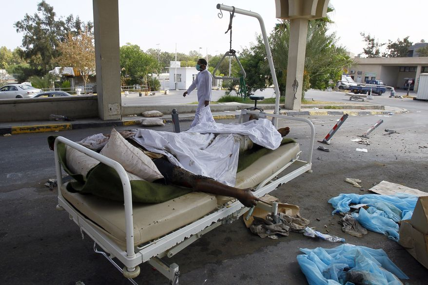 Libyan dead bodies lay in the hospital of Abu Salim district, in Tripoli, Libya, on Aug. 26, 2011. The four-story hospital was completely empty with shattered glass over the floors, dark with dried blood stains and with medical equipment strewn about. In the hospital yard next to the parking lot is a pile of 20 decomposing bodies, all of them darker skinned than most Libyans, covered with blankets. Gadhafi had recruited fighters from sub-Saharan Africa. (Associated Press)