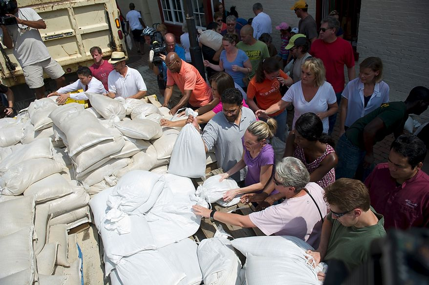 People grasp for sand bags from a city maintenance truck at the corner of King and N. Lee Streets in Old Town Alexandria, Va, Friday, August 26, 2011. In a city which saw severe flooding during Hurricane Isabel in 2002, business owners and residents are wasting no time preparing for Hurricane Irene. (Rod Lamkey Jr./The Washington Times)