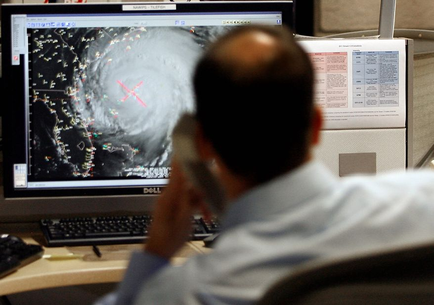 Hurricane specialist Dan Brown reviews the tracks and intensity of Hurricane Irene at the National Hurricane Center on Friday, August 26, 2011, in Miami.The hurricane warning was extended into the Chesapeake Bay as far as Drum Point, and existing warnings remained in effect from North Carolina to New Jersey. A hurricane watch was in effect even farther north and included Long Island, Martha's Vineyard and Nantucket, Mass.   (AP Photo/Jeffrey M. Boan)