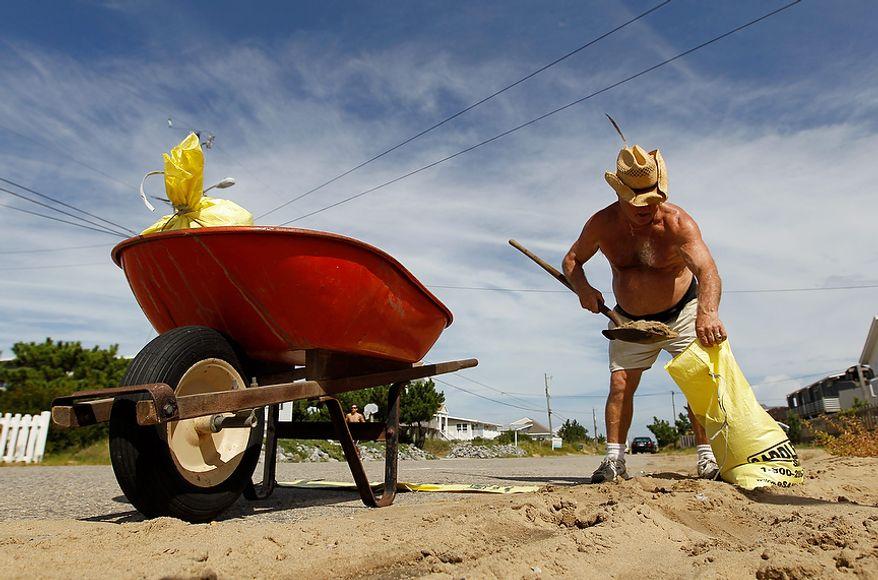 Sandbridge resident Sonny Latulipe fills sandbags in preparation for the arrival of Hurricane Irene in Virginia Beach, Va., Friday, Aug. 26, 2011. Hurricane Irene is expected to hit the area Saturday.  (AP Photo/Steve Helber)