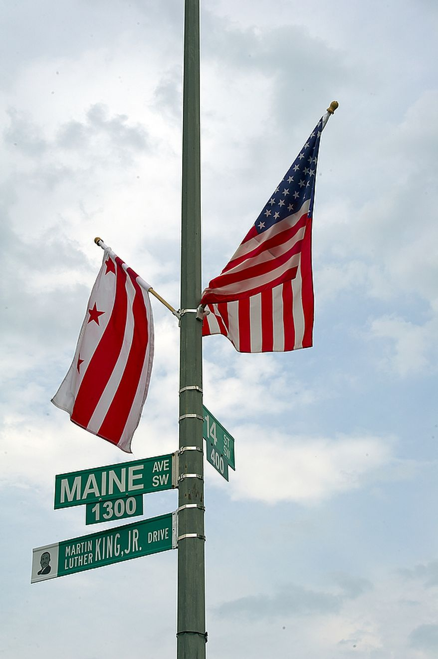 The newly unveiled Martin Luther King Jr. Drive sign sits below the Maine Avenue S.W. sign at the corner of Maine Avenue and 14th Street S.W. on Thursday, Aug. 25, 2011, the day that this part of Maine Avenue was officially renamed. The road will continue along the Southwest Freeway and join up with the other part of Martin Luther King Jr. Drive in Southeast. The sign is unusual in that it has a likeness of Dr. King on it. (Barbara L. Salisbury/The Washington Times)