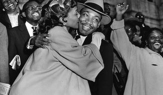 The Rev. Martin Luther King Jr. is welcomed with a kiss by his wife Coretta after leaving court in Montgomery, Ala., March 22, 1956.  King was found guilty of conspiracy to boycott city buses in a campaign to desegregate the bus system, but a judge suspended his $500 fine pending appeal. (AP Photo/Gene Herrick)