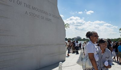 """My children aren't going to get this in a classroom,"" said Lola Martin, left, of Queens, N.Y., of the history evoked by the Martin Luther King Jr. Memorial in Washington, D.C. Here she poses for a picture at the memorial with Ron Smith of Washington, D.C. on Monday, Aug. 22, 2011, the day the memorial opened to the public. ""This memorial is my ancestors' blood,"" said Smith. The two are members of brother and sister social fellowships, Groove Phi Groove and Swing Phi Swing, respectively, and just met for the first time but decided to come down to the memorial together. (Barbara L. Salisbury/The Washington Times)"
