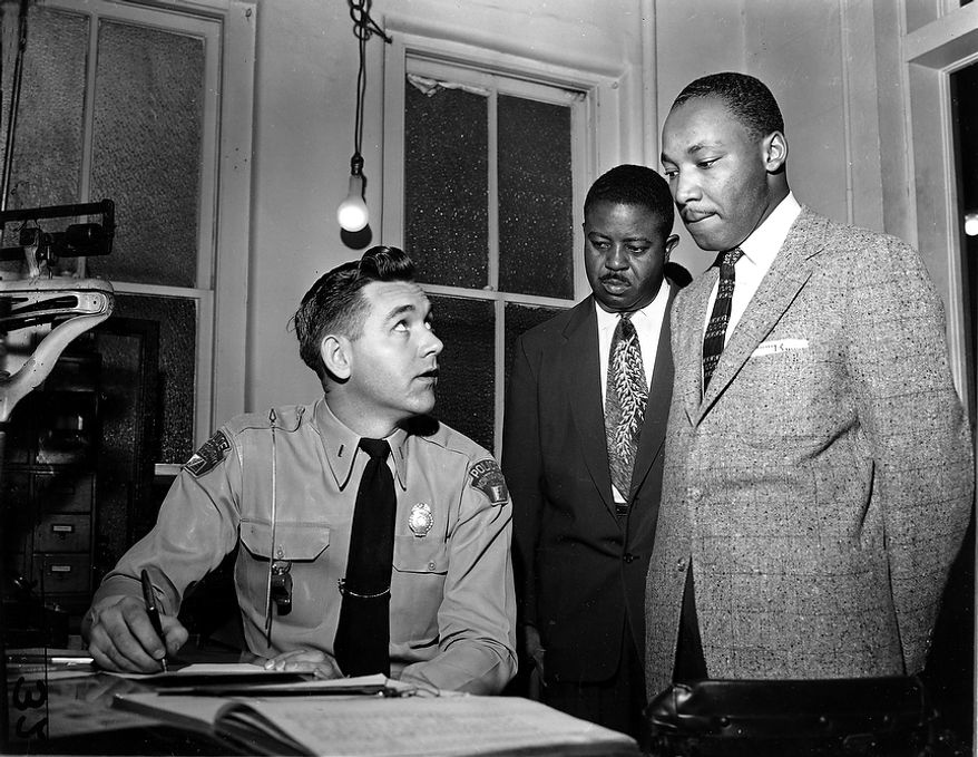 The Rev. Martin Luther King Jr., right, accompanied by Rev. Ralph D. Abernathy, center, is booked by city police Lt. D.H. Lackey in Montgomery, Ala., on Feb. 23, 1956.  The civil rights leaders are arrested on indictments turned by the Grand Jury in the bus boycott.  (AP Photo/Gene Herrick)