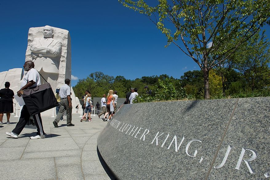 """it's amazing to be here today,"" said Washington, D.C. native Michael Berry, seen here walking past the sculpture of Dr. Martin Luther King Jr., who was first in line to see the new Martin Luther King Jr. Memorial when it opened to the public on Monday, Aug. 22, 2011. Mr. Berry says he was 13 when Dr. King was assassinated, and he remembers the riots and the impact they had on his neighborhood, his city and the nation. He says he'll be coming down again on Sunday for the dedication. (Barbara L. Salisbury/The Washington Times)"