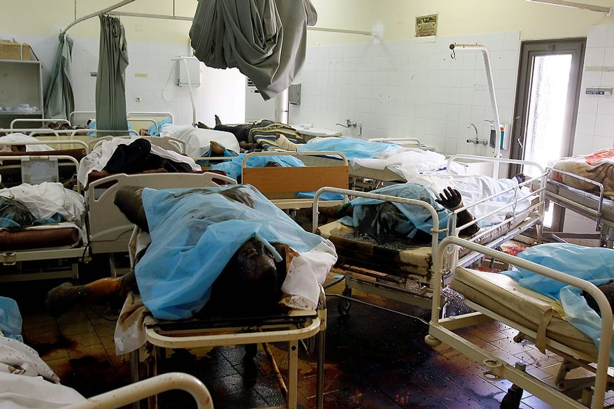 Lifeless bodies lay as they are placed at the hospital in the Abu Salim district in Tripoli, Libya, Friday, Aug. 26, 2011. The four-storey hospital was completely empty with shattered glass over the floors, dark with dried blood stains and with medical equipment strewn about. (AP Photo/Francois Mori)