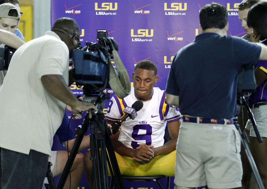 This Aug. 9, 2011 file photo shows LSU quarterback Jordan Jefferson talking to reporters during NCAA college football media day in Baton Rouge, La. Police have issued arrest warrants charging LSU quarterback Jordan Jefferson and a teammate, Joshua Johns, with second-degree battery for a bar fight that injured four people last week. Baton Rouge police Sgt. Don Stone said in a statement Friday, Aug. 26, 2011, that investigators have contacted the players' attorney, Nathan Fisher, and LSU coach Les Miles, and asked for the players to turn themselves in. (AP Photo/Gerald Herbert, File)