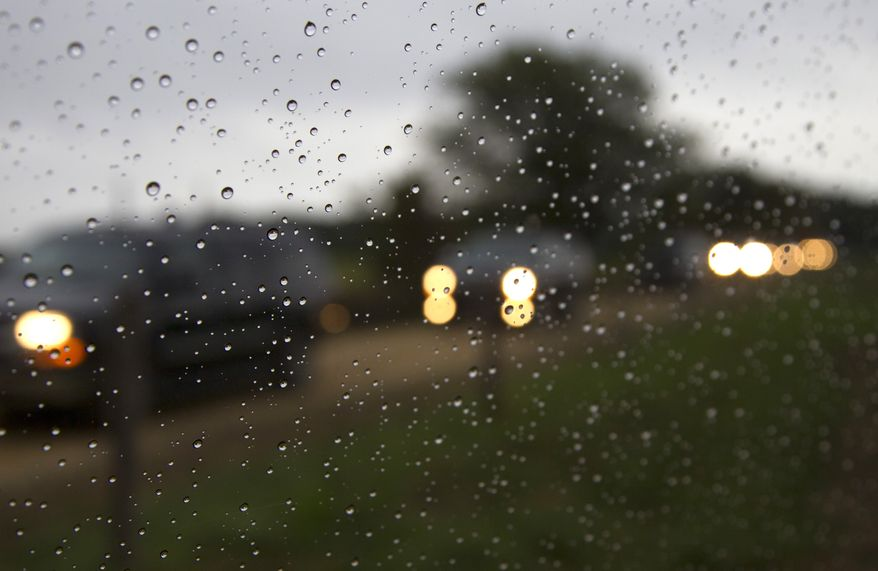 A motorcade with President Obama aboard, seen through the rainy pool van window, moves from Blue Heron Farm in Chilmark on Martha's Vineyard, Mass., on Aug. 25, 2011. (Associated Press)