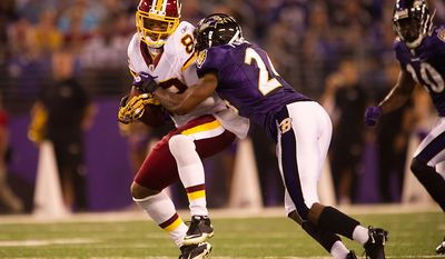 Receiver Santana Moss of the Washington Redskins is hit hard on a short pass by cornerback Domonique Foxworth of the Baltimore Ravens in  preseason football at M&T Bank Stadium in Baltimore, MD, Thursday, August 25, 2011. (Andrew Harnik / The Washington Times)
