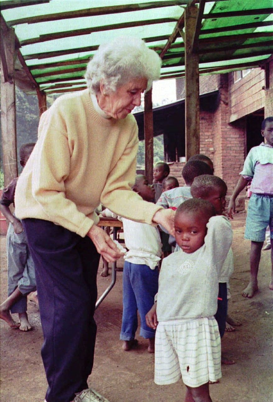 **FILE** Rosamund Carr attends to an orphan at her flower plantation and orphanage at the foot of the Virunga volcano range in Mutara, Rwanda, on July 4, 1996. (Associated Press)