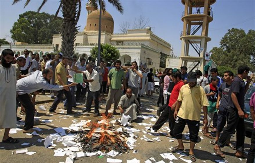 Rebel supporters burn Green books in the main square of the Qasr Bin Ghashir district in Tripoli, Libya, Saturday, Aug. 27, 2011. Libyan rebel leaders say they have taken control of a strategic border crossing with Tunisia, but are still meeting resistance from regime loyalists along the coastal road between the border and the capital. (AP Photo/Sergey Ponomarev)