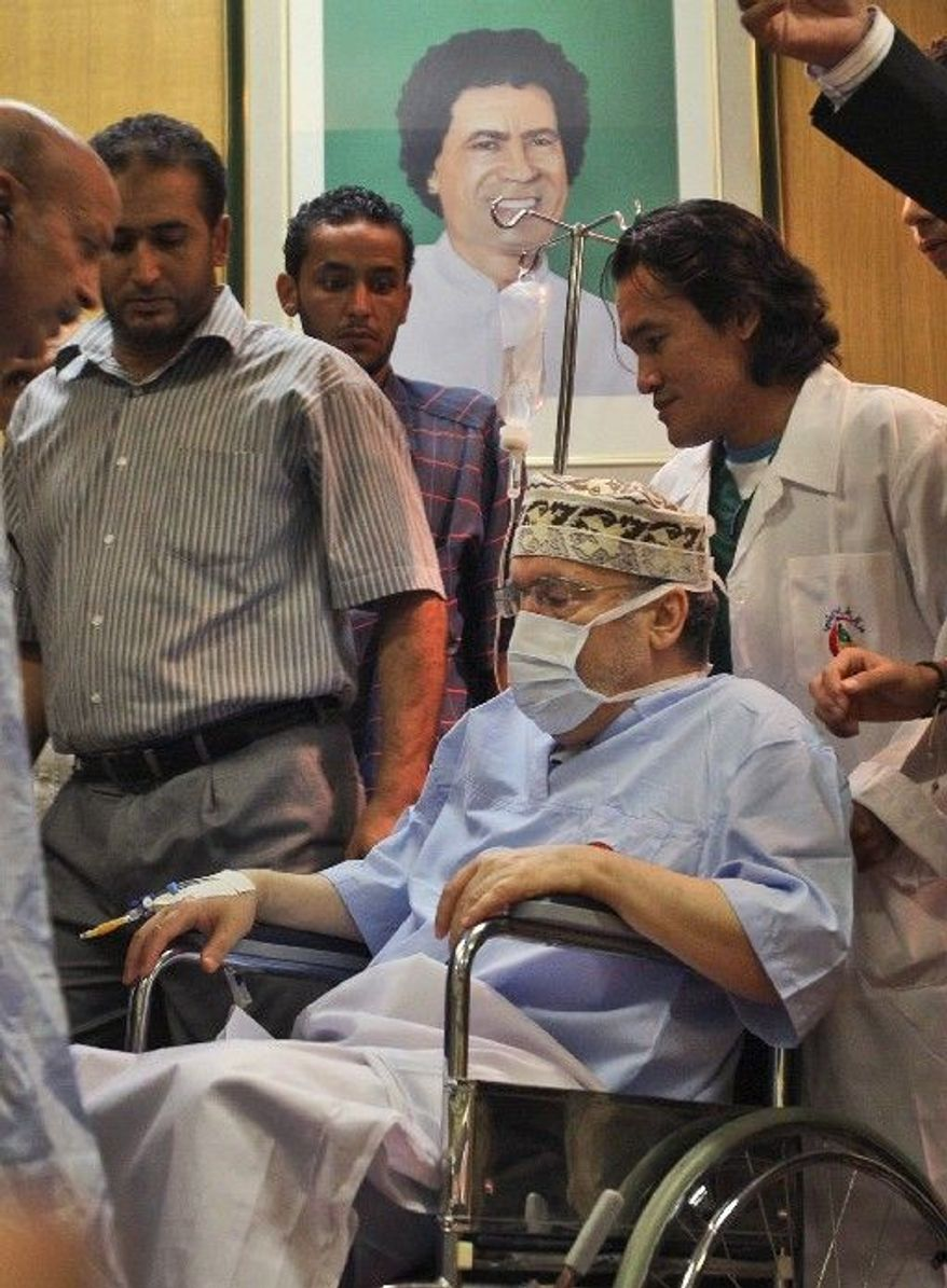 ASSOCIATED PRESS Abdel Baset al-Megrahi, who was found guilty of the 1988 Lockerbie bombing but released on compassionate grounds, is seen below a portrait of Moammar Gadhafi as he is visited by African parliamentarians at Tripoli Medical Center.