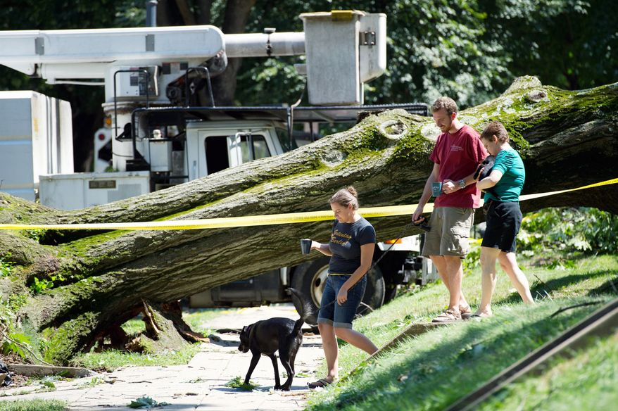 Neighbor Lisa Gelhaus (right) talks to D.C. resident Kevin Gibbons and his wife, Ashley Domm, on Sunday after a tree damaged the couple's apartment building in Glover Park. (Andrew Harnik/The Washington Times)