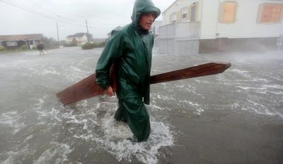 STANDARD TIMES VIA ASSOCIATED PRESS Chris Swimm on Sunday retrieves planks from a friend's deck in Fairhaven, Mass., that were washed away by Tropical Storm Irene. With sustained winds of 50 mph, Irene was downgraded from hurricane strength by the time it reached New England.