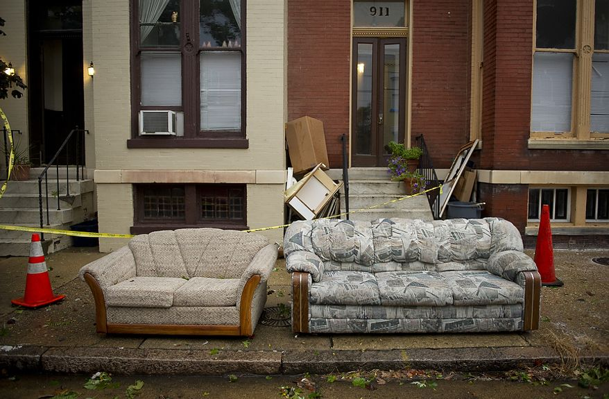 Soaked couches sit on the curb on Prince Street in Alexandria on Sunday, Aug. 28, 2011, as Hurricane Irene makes its exit from the region and points northward along the Atlantic coast. (Rod Lamkey Jr./The Washington Times)