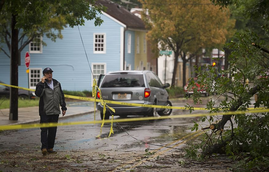 An Alexandria city worker who did not wish to give his name checks out the scene where tree branches and a telephone line came down on Payne Street between Prince and Commerce streets in Alexandria on Sunday, Aug. 28, 2011. (Rod Lamkey Jr./The Washington Times)
