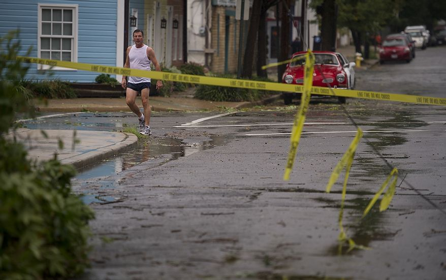 A runner pauses to check out the scene where tree branches and a telephone line came down on Payne Street between Prince and Commerce streets in Alexandria on Sunday, Aug. 28, 2011. (Rod Lamkey Jr./The Washington Times)