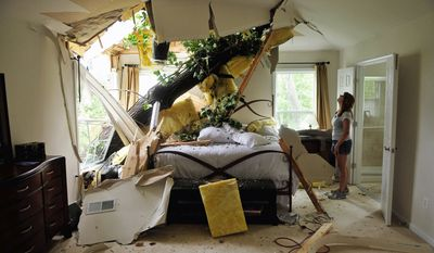 UNWELCOME VISITOR: Debbie Martinez looks over the damage caused by a tree uprooted by Hurricane Irene that crashed into the bedroom of the house she is renting on Canal Lane in White Hall Manor, in Annapolis on Sunday. Nobody was hurt. (J.M. Eddins/The Washington Times)