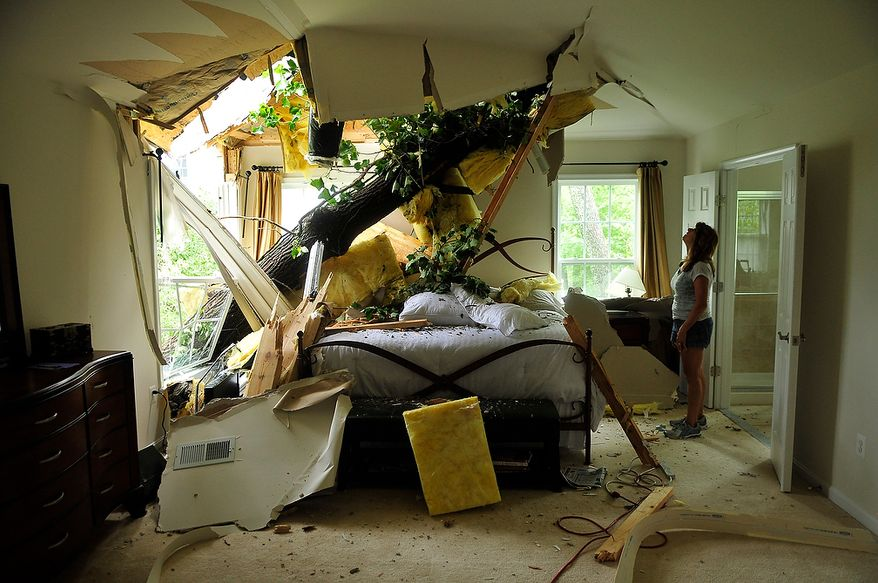 Debbie Martinez looks over the damage caused by an uprooted tree which crashed into the bedroom of the house she is renting on Canal Lane in White Hall Manor, in Anne Arundel County, Md., Sunday, August 28, 2011. Winds and rain from Hurricane Irene uprooted trees which crashed into houses in the neighborhood on Saturday night, August 27, 2011. Nobody was hurt in the incident. (J.M. Eddins, Jr./The Washington Times)