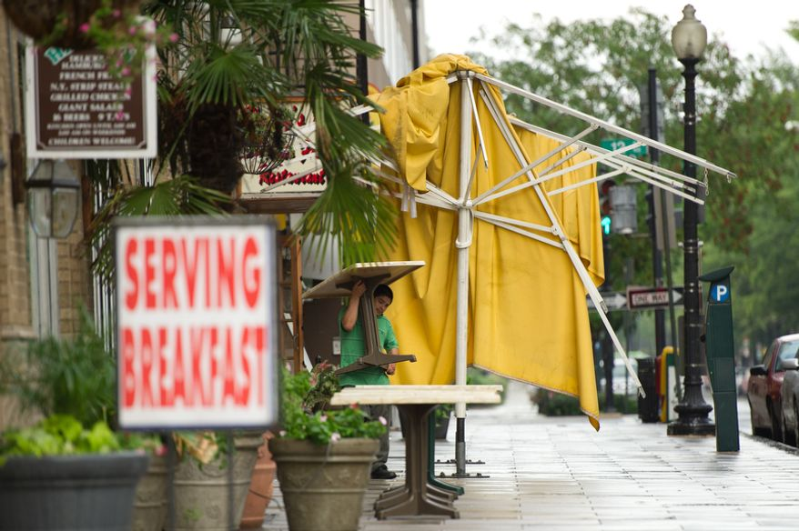 A man sets up tables for breakfast next to damaged awnings at Harry's in downtown Washington, DC, Sunday, August 28, 2011. (Andrew Harnik / The Washington Times)