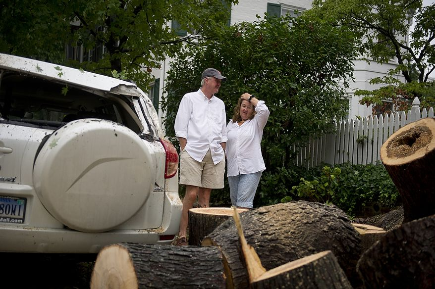 Anne Craner (left) chats with her husband, Lorne, where a maple tree fell in front of their home on Princess Street and damaged a Toyota Rav4 during Hurricane Irene in Old Town Alexandria, Va., Sunday, August 28, 2011. (Rod Lamkey Jr./The Washington Times)
