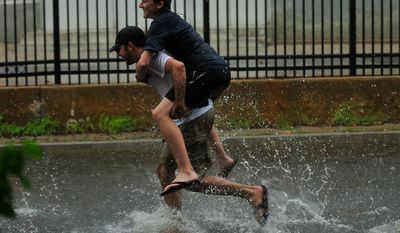 Kevin Gaughan, of Annapolis, Md.,  carries Kristin Barth of Baltimore, Md. through flood waters on Prince George Street as bands of high winds and heavy rain from Hurricane Irene lash Annapolis, Md., Saturday, August 27, 2011. (J.M. Eddins, Jr./The Washington Times)