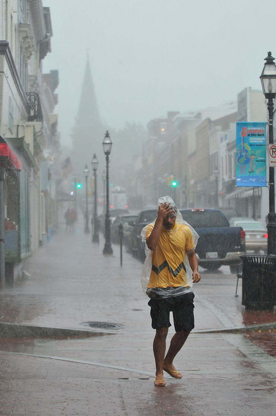 Omar Said, 24, walks down Main Street covered in a plastic bag as bands of high winds and heavy rain from Hurricane Irene lash Annapolis, Md., Saturday, August 27, 2011. (J.M. Eddins, Jr./The Washington Times)