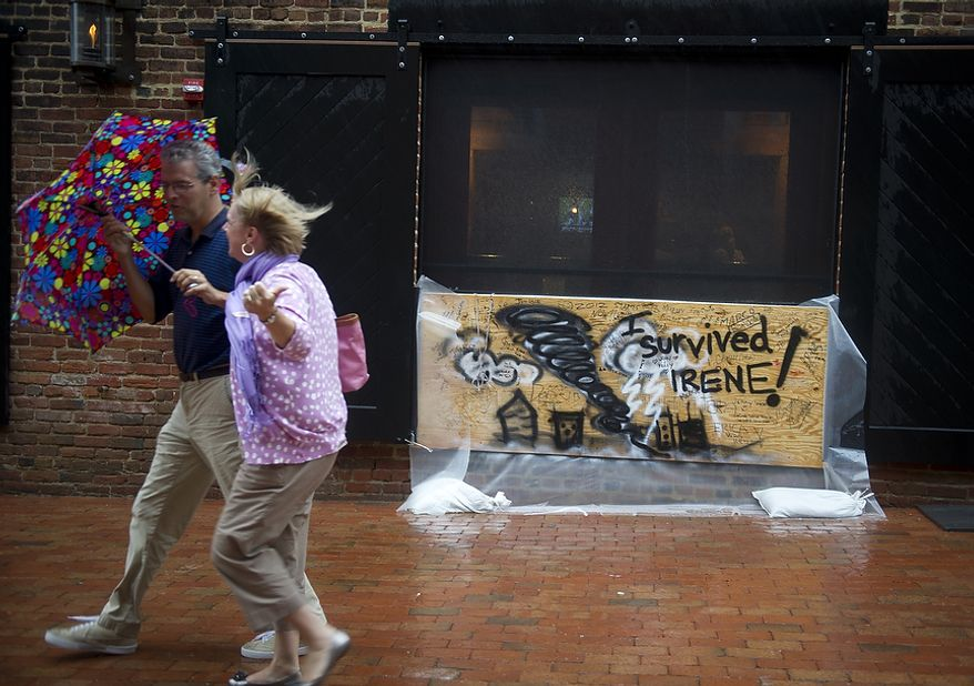 As Hurricane Irene makes her way up the Atlantic coast, a couple passes a message board in Old Town Alexandria, Va, Saturday, August 27, 2011. (Rod Lamkey Jr./The Washington Times)