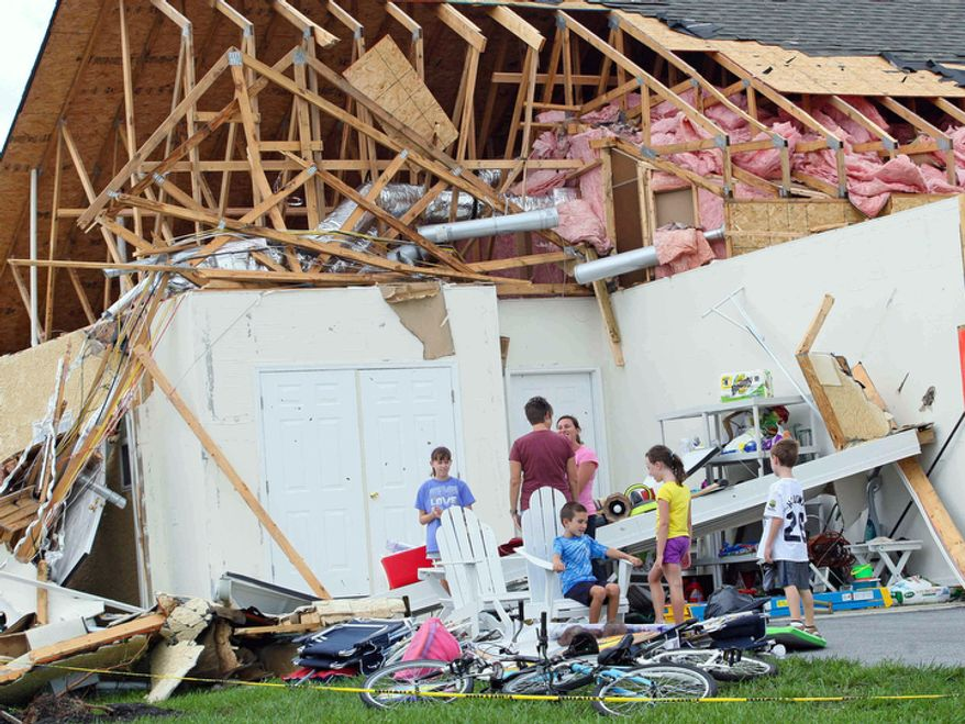 People look over the damage to Sue and Jack Holloway's home on Crab Apple Court in the Nassau Station development in Lewis, Del. Sunday, Aug. 28, 2011.  (AP Photo/The News Journal, Suchat Pederson)