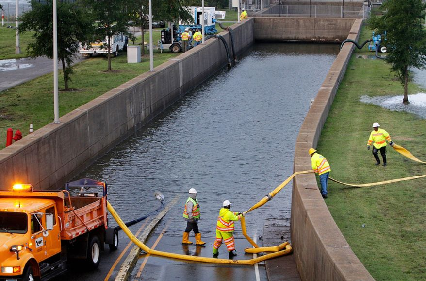 Virginia Dept. of Transportation workers place hose to pump out floodwater at the entrance of Midtown Tunnel prior to its scheduled opening in Norfolk, Va. Sunday morning, Aug. 28, 2011. (AP Photo/The Virginia-Pilot, Hyunsoo Leo Kim)  MAGS OUT