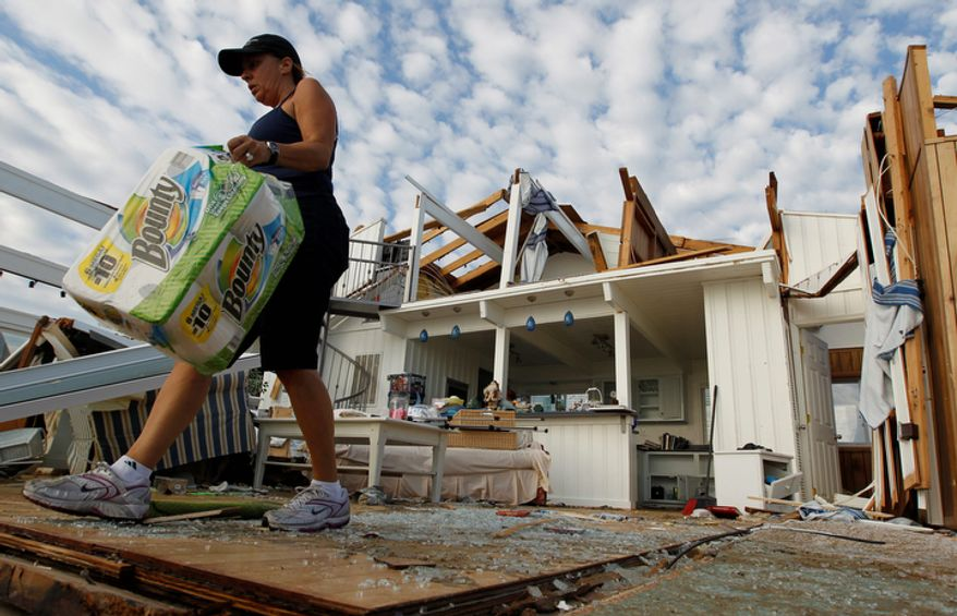 Denise Robinson clears out her destroyed beach home in the Sandbridge area of Virginia Beach. (AP Photo/Steve Helber)