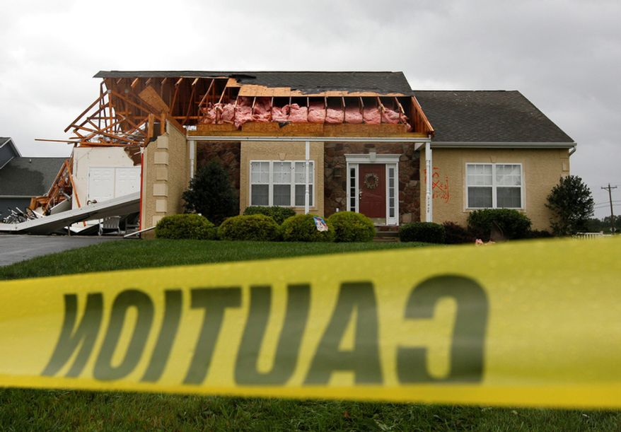 Caution tape hangs in front of a house that was heavily damaged by a possible tornado in Lewes, Del., Sunday, Aug. 28, 2011, after Hurricane Irene churned along the Delaware coast overnight. (AP Photo/Patrick Semansky)