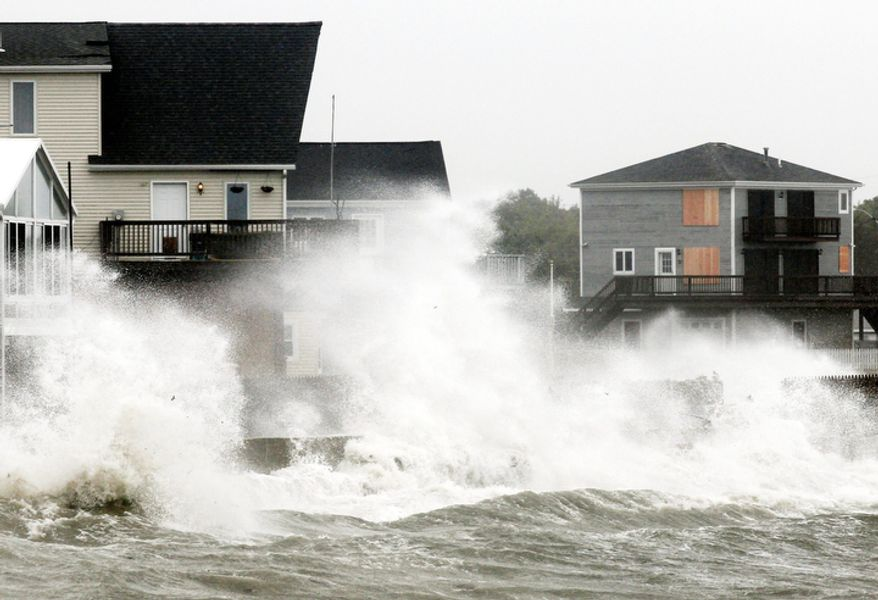 Waves crash along a seawall as Tropical Storm Irene, downgraded from a hurricane, slammed into Fairhaven, Mass. Sunday, Aug. 28, 2011.  (AP Photo/Winslow Townson)