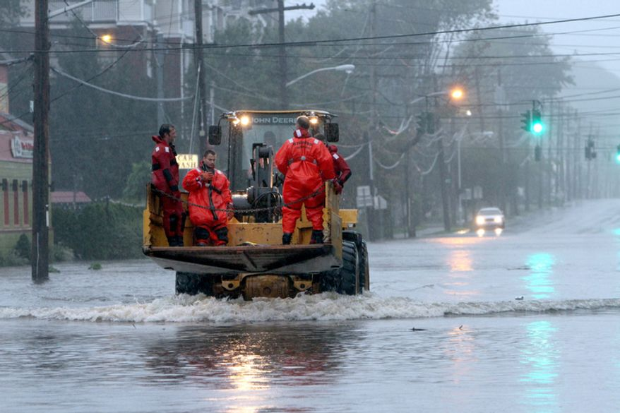 Village of Mamaroneck, N.Y. rescue swimmers ride on the front of a pay-loader en-route to their next mission during Hurricane Irene in Mamaroneck during Hurricane Irene Sunday, Aug. 28, 2011.  ( AP Photo/The Journal News, Frank Becerra Jr)
