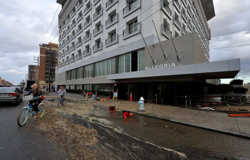 Bicyclists ride past the Allegria Hotel on West Broadway which was flooded from Hurricane Irene that swept through Long Island on Sunday, Aug. 28, 2011, in Long Beach, N.Y.  (AP Photo/Kathy Kmonicek)