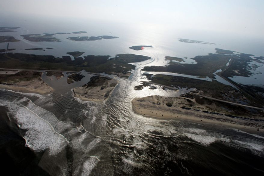 A flooded road is seen in Hatteras Island, N.C., Sunday, Aug. 28, 2011after Hurricane Irene swept through the area Saturday cutting the roadway in five locations.  (AP Photo/Jim R. Bounds)