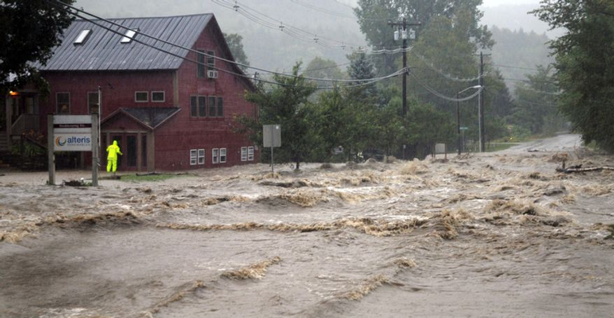 A person searches for anyone who may be occupying the building as raging flood waters from Tropical Storm Irene cross Route 100, closing the main road to traffic in Waitsfield, Vt., Sunday, Aug. 28, 2011. (AP Photo/Sandy Macys)