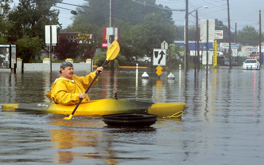 Kevin Holligan, of the Staten Island borough of New York, kayaks across a flooded section of the borough's Hyland Boulevard after the rain and wind of Tropical Storm Irene subsided, Sunday, Aug. 28, 2011 on Staten Island, N.Y. (AP Photo/The Staten Island Advance, Anthony DePrimo)