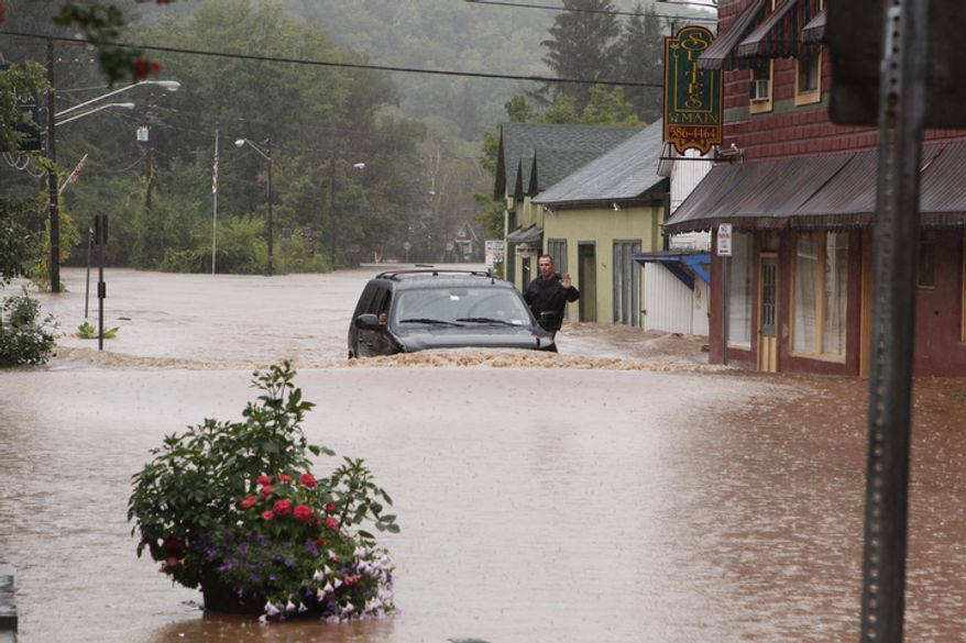 A security guard hangs on the door of Gov. Andrew Cuomo's SUV in the middle of a flooded street Sunday, Aug. 28, 2011, in Margaretville, N.Y. Gov. Cuomo was riding in the SUV, and posted some photos of the heavy flooding on his flickr site.  (AP Photo/Dick Sanford)