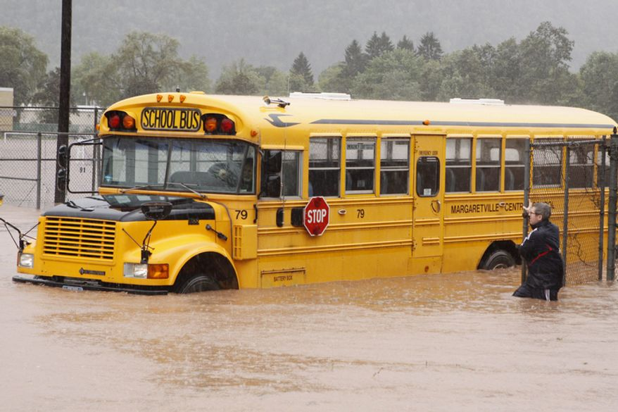 Margaretville Central School Athletic Director Jeremey Marks stands next to a school bus in floodwaters Sunday, Aug. 28, 2011, in Margaretville, N.Y.  (AP Photo/Dick Sanford)