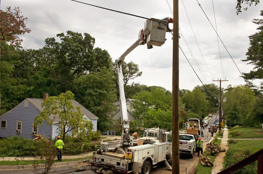 Workers with C.W. Wright Construction Company, a subcontractor for Pepco, work to secure a newly installed power line on Woodland Avenue in Takoma Park on Monday, while tree specialists with Arbor Care Inc. remove pieces of a large tree that knocked down the lines on this residential street. (Barbara L. Salisbury/The Washington Times)