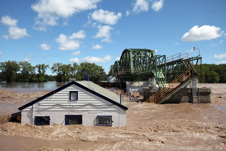 Lock 8 in Rotterdam, N.Y. overflows with water, and a metal barge is crashed into the gates, on Monday, Aug. 29, 2011 during extensive flooding in the region as a result of Tropical Storm Irene.  (AP Photo/The Daily Gazette, Patrick Dodson)