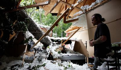 Chester Vickers surveys the bedroom of his girlfriend's daughter, which was heavily damaged by a tree that fell in high winds caused by Hurricane Irene in Port Deposit, Md., Monday, Aug. 29, 2011. (AP Photo/Patrick Semansky)