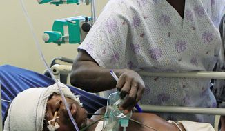 ASSOCIATED PRESS A nurse at the national hospital in Abuja, Nigeria, removes the breathing mask of a man injured in Friday's suicide attack on U.N. headquarters in Abuja so he can speak during a visit by U.N. Deputy Secretary-General Asha-Rose Migiro (not seen) on Sunday. Twenty-three died in the suicide car bombing.